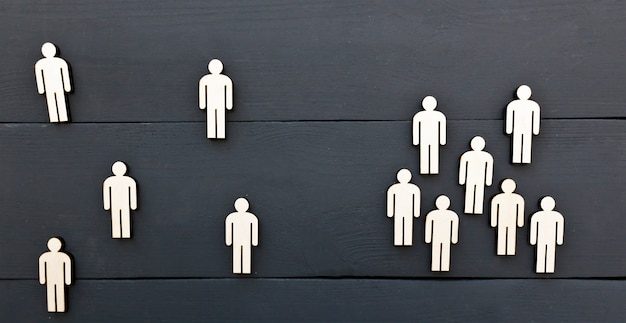 Concept de la distance sociale entre les personnes. un groupe de personnes en bois se tient séparément des personnes de l'anogroupe