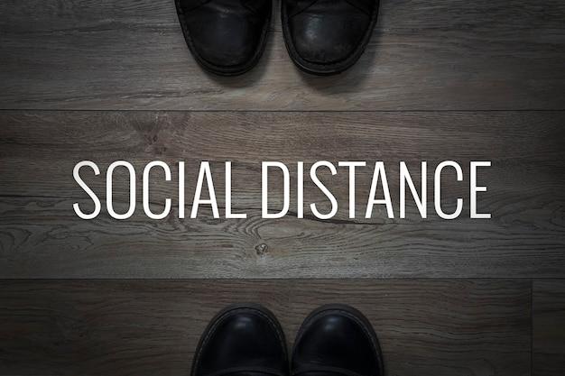 Concept de distanciation sociale. chaussures sur le sol et l'inscription distance sociale sur le fond du sol sur fond sombre. distance dangereuse. violations de l'espace personnel