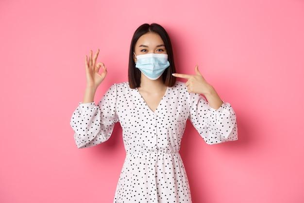 Concept de distanciation sociale et de mode de vie du coronavirus jolie femme asiatique pointant sur un masque facial montrant o...