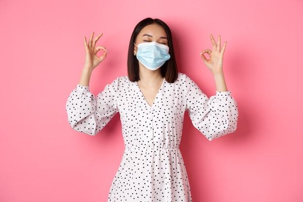 Le concept de distanciation sociale et de mode de vie du coronavirus satisfait une femme asiatique en masque facial montrant bien ...