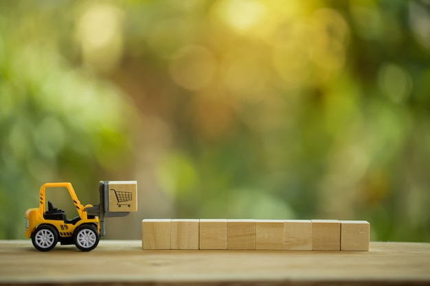 Concept de distribution de réseau logistique et de fret: un mini-chariot élévateur déplace une palette avec un bloc en bois avec une icône. décrit la livraison de biens ou de produits dans le monde entier dans le commerce électronique.
