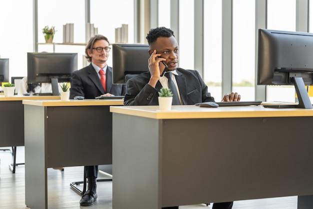 Concept de diversité d'entreprise et de travail. homme d'affaires africain parlant sur appel avec smartphone mobile et travaillant avec un ordinateur de bureau.