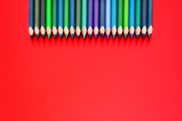Concept de diversité. ligne de crayon de couleur de mélange sur fond rouge