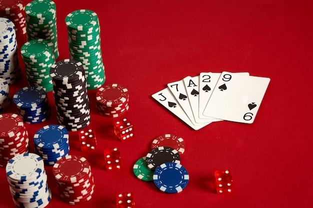 Concept de divertissement et d'équipement de poker de jeu de casino - gros plan sur des cartes à jouer et des jetons sur fond rouge. affleurer. fond de casino. espace de copie. nature morte