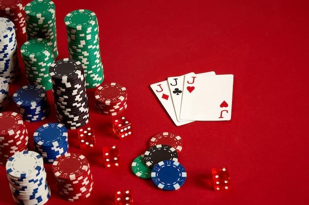 Concept de divertissement et d'équipement de poker de jeu de casino - gros plan sur des cartes à jouer et des jetons sur fond rouge. un brelan. fond de casino. espace de copie. nature morte