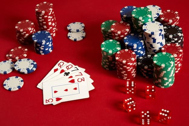 Concept de divertissement et d'équipement de poker de jeu de casino - gros plan sur des cartes à jouer et des jetons sur fond rouge. deux paires. fond de casino. espace de copie. nature morte