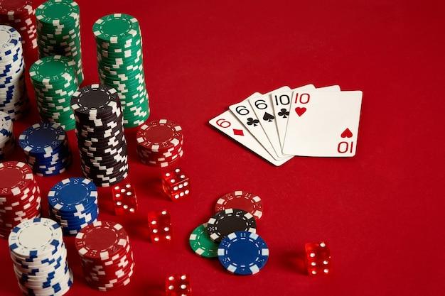 Concept de divertissement et d'équipement de poker de jeu de casino - gros plan sur des cartes à jouer et des jetons sur fond rouge. full house. fond de casino. espace de copie. nature morte