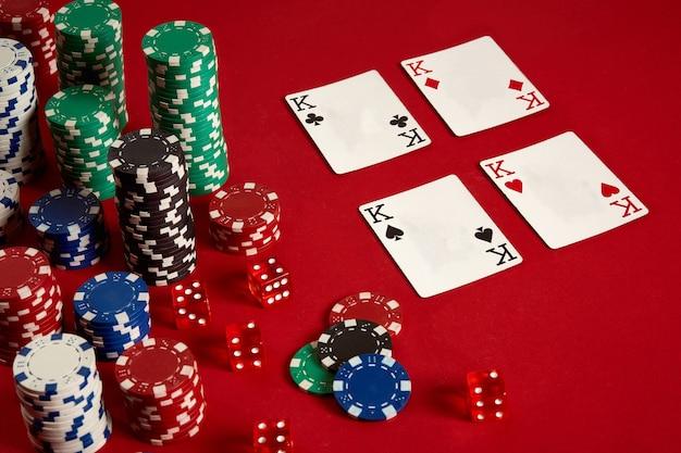 Concept de divertissement et d'équipement de poker de jeu de casino - gros plan sur des cartes à jouer et des jetons sur fond rouge. quatre d'un genre. fond de casino. espace de copie. nature morte