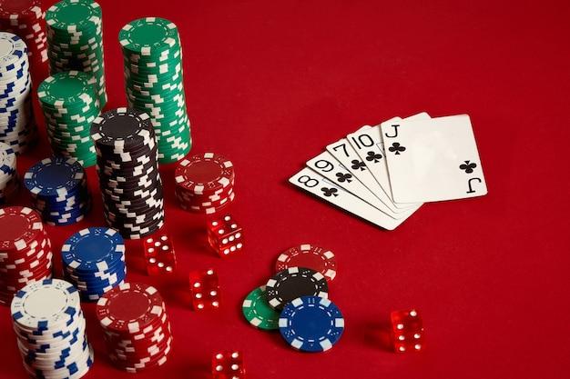 Concept de divertissement et d'équipement de poker de jeu de casino - gros plan sur des cartes à jouer et des jetons sur fond rouge. quinte flush. fond de casino. espace de copie. nature morte