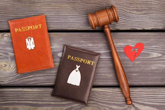 Concept de divorce de contrat de mariage. marteau avec passeports et cœur brisé.