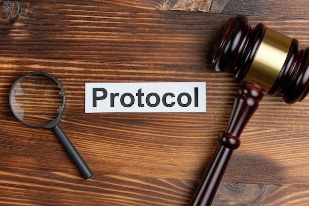 Concept d'un document judiciaire en tant que protocole à côté de la loupe et du marteau du juge