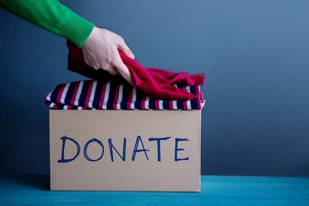 Concept de don. femme préparant ses vieux vêtements usés dans une boîte à dons