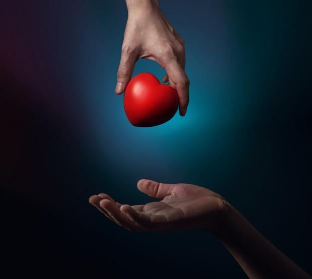 Concept de don. une main de donateur donnant un coeur rouge au bénéficiaire. signe de don