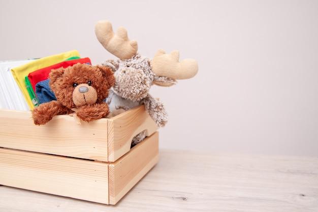 Concept de donation. donnez une boîte avec des vêtements pour enfants, des livres, des fournitures scolaires et des jouets.