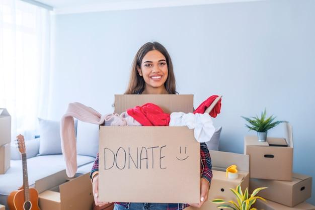Concept de donation. femme tenant une boîte de dons avec plein de vêtements