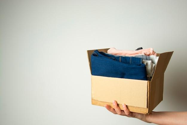 Concept de donation. mains tenant une boîte de don avec des vêtements. espace de copie.