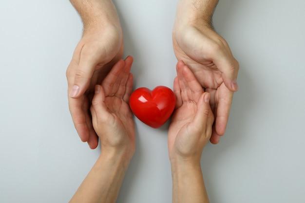 Concept de donneur avec les mains tenant le coeur rouge sur fond blanc