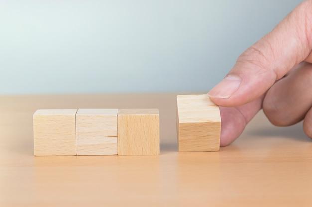 Concept de douleur ou de gain, cube de bois flip à la main