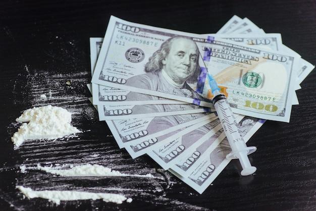 Concept de drogue, dollar, argent, toxicomanie et toxicomanie - fermez la seringue avec une cuillère et une dose de drogue de crack