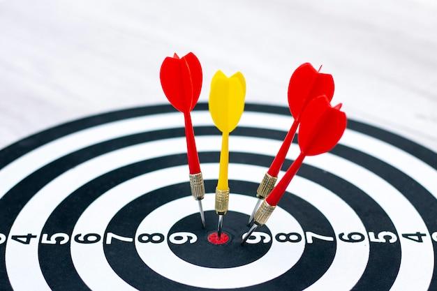 Concept de droit de cible à l'aide de fléchettes dans bullseye. une flèche en bulseye, trois flèches rouges sont tombées