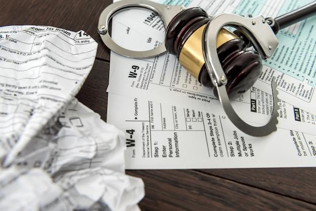 Concept de droit, formulaire d'impôt financier 1040 avec marteau et menottes