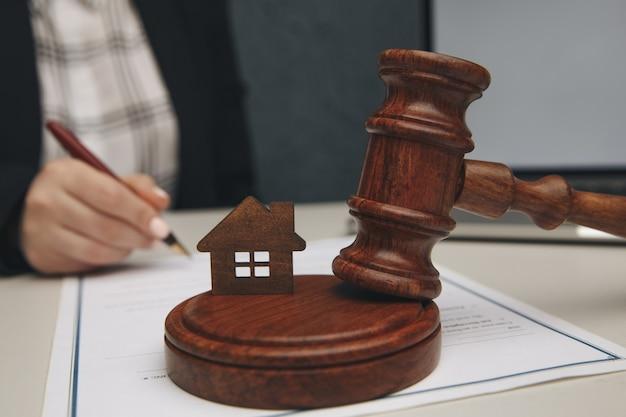 Concept de droit immobilier. maquette de maison et un marteau.