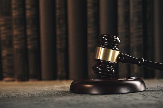 Concept de droit - livre de droit ouvert avec un marteau de juges en bois sur une table dans une salle d'audience ou un bureau des forces de l'ordre sur fond noir.