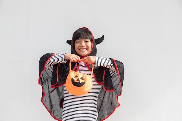 Concept drôle d'enfant d'halloween, petite fille mignonne avec le fantôme d'halloween de costume effrayant il tenant le fantôme orange de citrouille sur la main, sur le fond blanc
