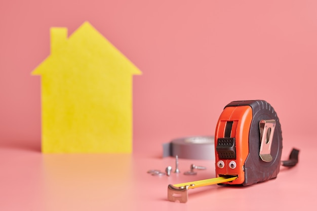 Concept drôle de ruban à mesurer en métal. rénovation de maison. réparation à domicile et concept redécoré. figure en forme de maison jaune