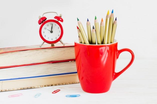 Concept du 1er septembre. réveil rouge, tasse, crayons de couleur, livres. concept de retour à l'école