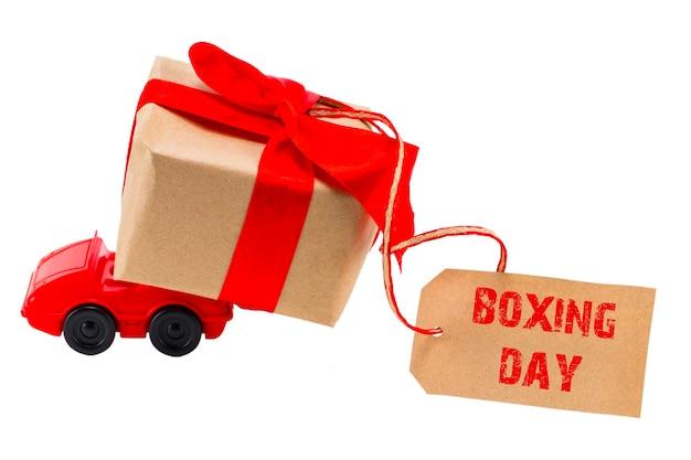 Le concept du boxing day. voiture jouet rouge offrant une boîte de cadeaux avec étiquette avec texte : boxing day sur fond blanc.