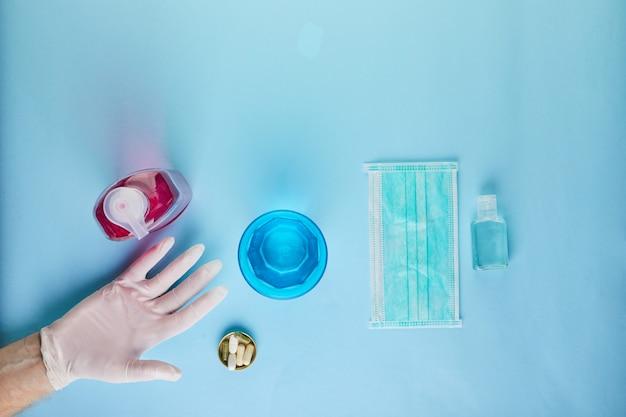 Le concept du coronavirus covid-19, comment vous protéger contre l'infection. le lavage des mains est pressé sur la main, le masque et les comprimés. mise à plat sur une table bleue