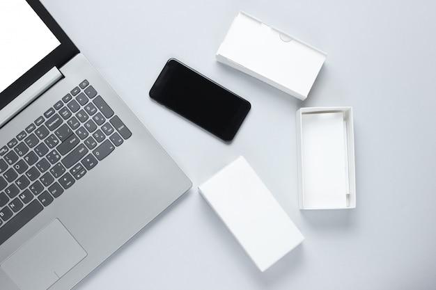 Le concept du déballage, des blogs techno. boîte avec nouveau smartphone, ordinateur portable sur surface grise.