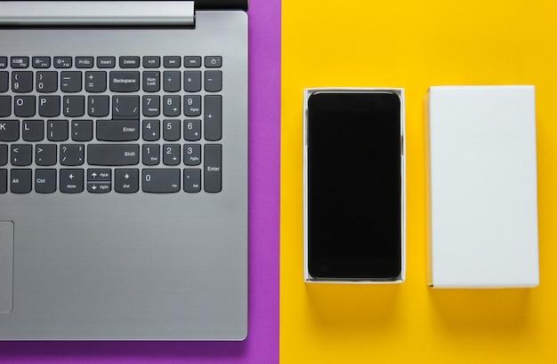 Le concept du déballage, des blogs techno. boîte avec un nouveau smartphone, ordinateur portable sur une surface jaune violet.