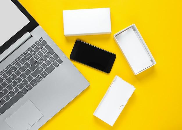 Le concept du déballage, des blogs techno. boîte avec un nouveau smartphone, ordinateur portable sur surface jaune.