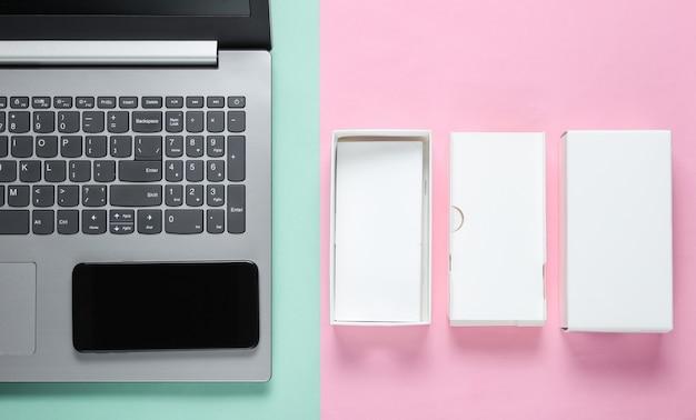 Le concept du déballage, des blogs techno. boîte avec un nouveau smartphone, ordinateur portable sur surface pastel.