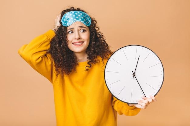 Concept du matin. belle jeune femme frisée étonnée choquée posant sur fond beige avec horloge et masque de sommeil.
