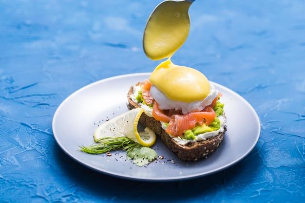Concept du matin et du petit-déjeuner - préparation d'un sandwich au saumon, une cuillère verse de la sauce dessus.