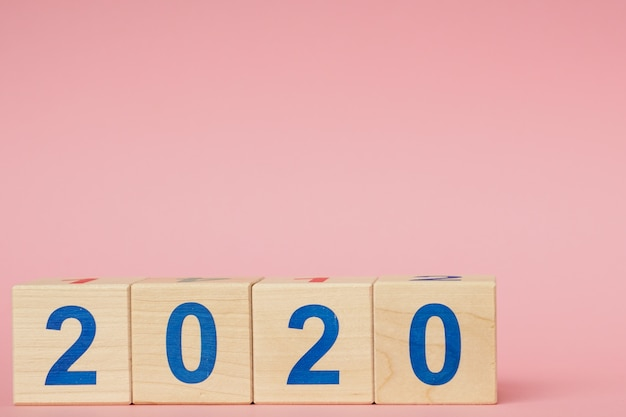 Concept du nouvel an 2020. cube de bloc en bois avec numéro sur table rose