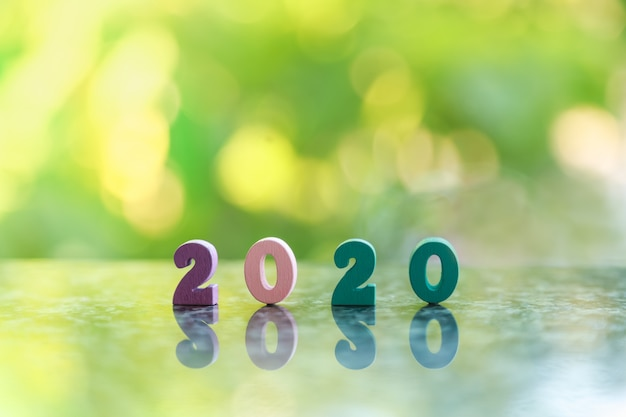 Concept du nouvel an 2020. gros plan du numéro en bois coloré sur le sol avec fond de nature feuille verte bokeh et copie espace pour le texte.