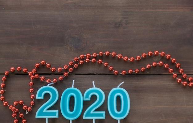 Concept du nouvel an 2020. vue de dessus du nombre de bougies bleu clair avec perle ornementale rouge sur planche de bois avec espace de copie.