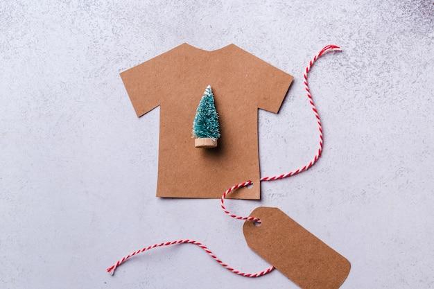 Concept du nouvel an. un t-shirt en carton découpé avec une étiquette sur une dentelle rouge-blanche avec un petit arbre de noël au centre.