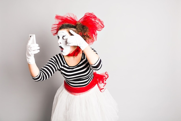 Concept du poisson d'avril. mime tenant un téléphone portable.