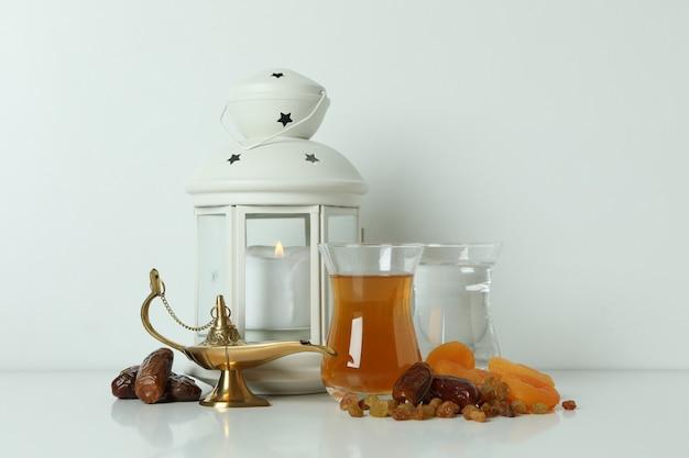 Concept du ramadan avec de la nourriture et des accessoires sur blanc