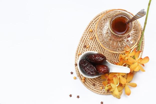 Concept du ramadan et quelques dates dans un bol ovarien avec service à thé et fleurs d'orchidées