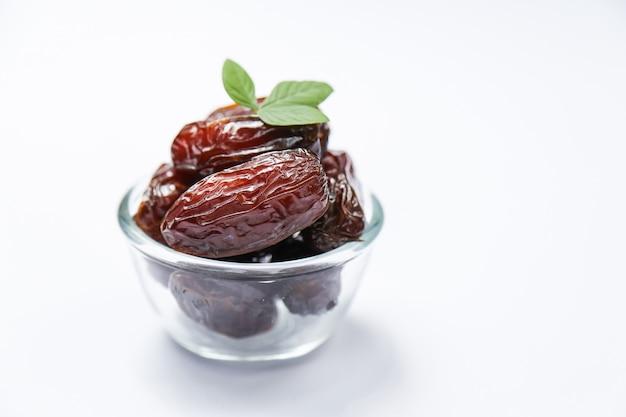 Concept du ramadan et quelques dates dans un bol transparent
