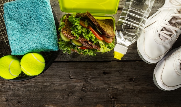 Concept du sport vie saine. sneakers avec boîte à lunch, serviette et bouteille d'eau sur fond en bois. espace de copie.