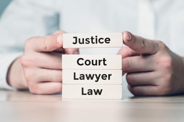Le concept du travail du système judiciaire sur des blocs de bois construits par une personne.