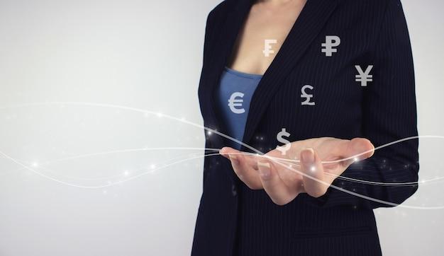 Concept d'échange de devises mondial. tenir à la main les monnaies du monde de l'hologramme numérique, la crypto-monnaie du portefeuille sur l'écran virtuel sur fond gris. échange de devises et analyse des marchés boursiers mondiaux
