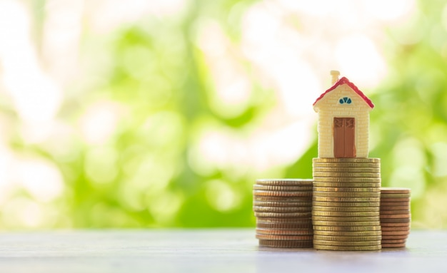 Concept d'échelle de propriété, maison et pile de pièces pour économiser pour acheter une maison
